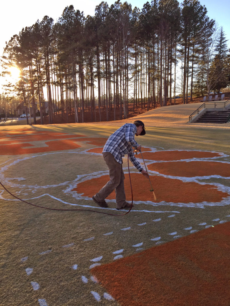 Man spray painting the Clemson Tiger paw logo at The Reserve