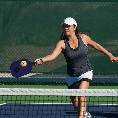 woman in grey tanktop playing pickleball